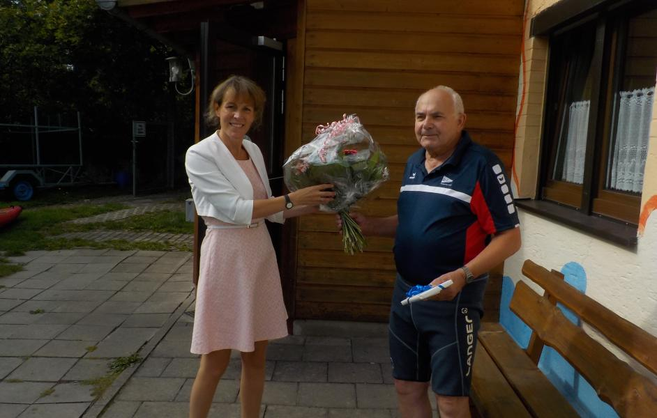 Eva Döhla überreicht Blumenstrauss an Karl Schmalz